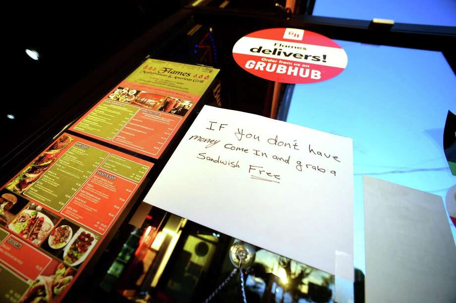 A sign on the front door of Flames Mediterranean & American Grill in Milford offers free sandwiches for those without money. Photo: Arnold Gold / Hearst Connecticut Media / New Haven Register