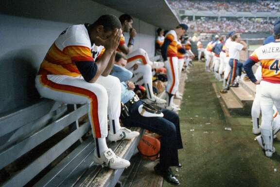 10/15/1986 -  The scene in the Houston Astros dugout moments after the final out at the National League Championship Series game 6 against the New York Mets in the Astrodome. Billy Hatcher buries his head in his hands and John Mizerock watches the Mets celebration on the field.