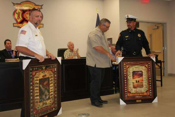 Dayton Mayor Jeff Lambright (center) presents pieces of artwork to Dayton Fire Chief Murphy Green (left) and Dayton Police Chief John Headrick at the start of the Oct. 16 city council meeting. The meeting was held in the new Dayton Fire Station on N. Cleveland St. following the grand opening of the fire station, police department and municipal court.