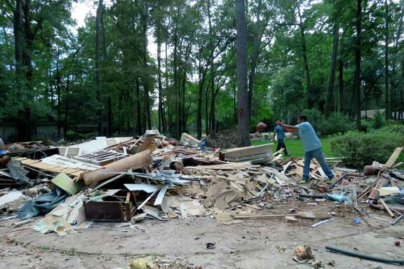 """In this Sept. 26, 2017 photo, workers continue clearing debris from the home of Houston resident Chris Slaughter, whose house in the suburb of Kingwood was flooded by 5 1/2 feet of water during Harvey's torrential rainfall. One month after the storm inundated Houston and damaged thousands of homes, Slaughter said he is almost ready to start rebuilding his house after having to rip everything out from the first floor. Slaughter says even though his family remains displaced from their home, he feels they are in a """"very good place in terms of everyone being safe, everyone having a path to get back to where we used to be."""" (AP Photo/Juan Lozano)"""