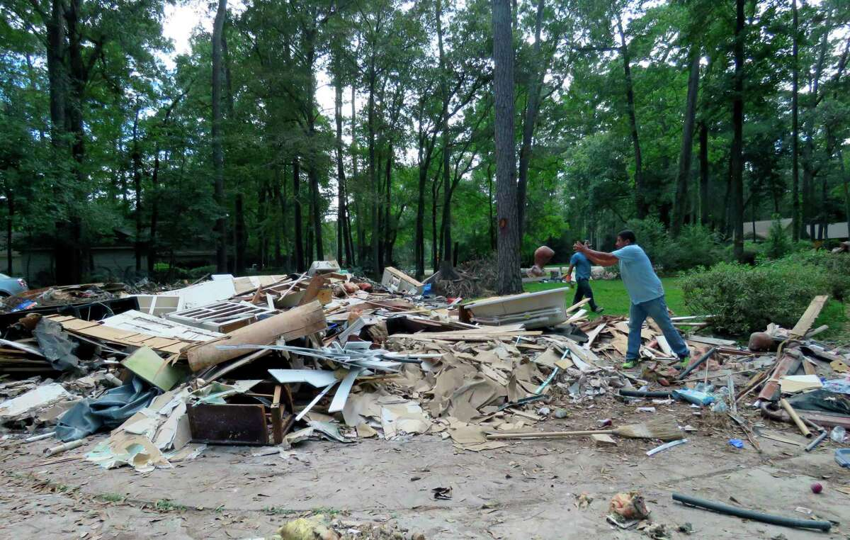 In this Sept. 26, 2017 photo, workers continue clearing debris from the home of Houston resident Chris Slaughter, whose house in the suburb of Kingwood was flooded by 5 1/2 feet of water during Harvey's torrential rainfall. One month after the storm inundated Houston and damaged thousands of homes, Slaughter said he is almost ready to start rebuilding his house after having to rip everything out from the first floor. Slaughter says even though his family remains displaced from their home, he feels they are in a