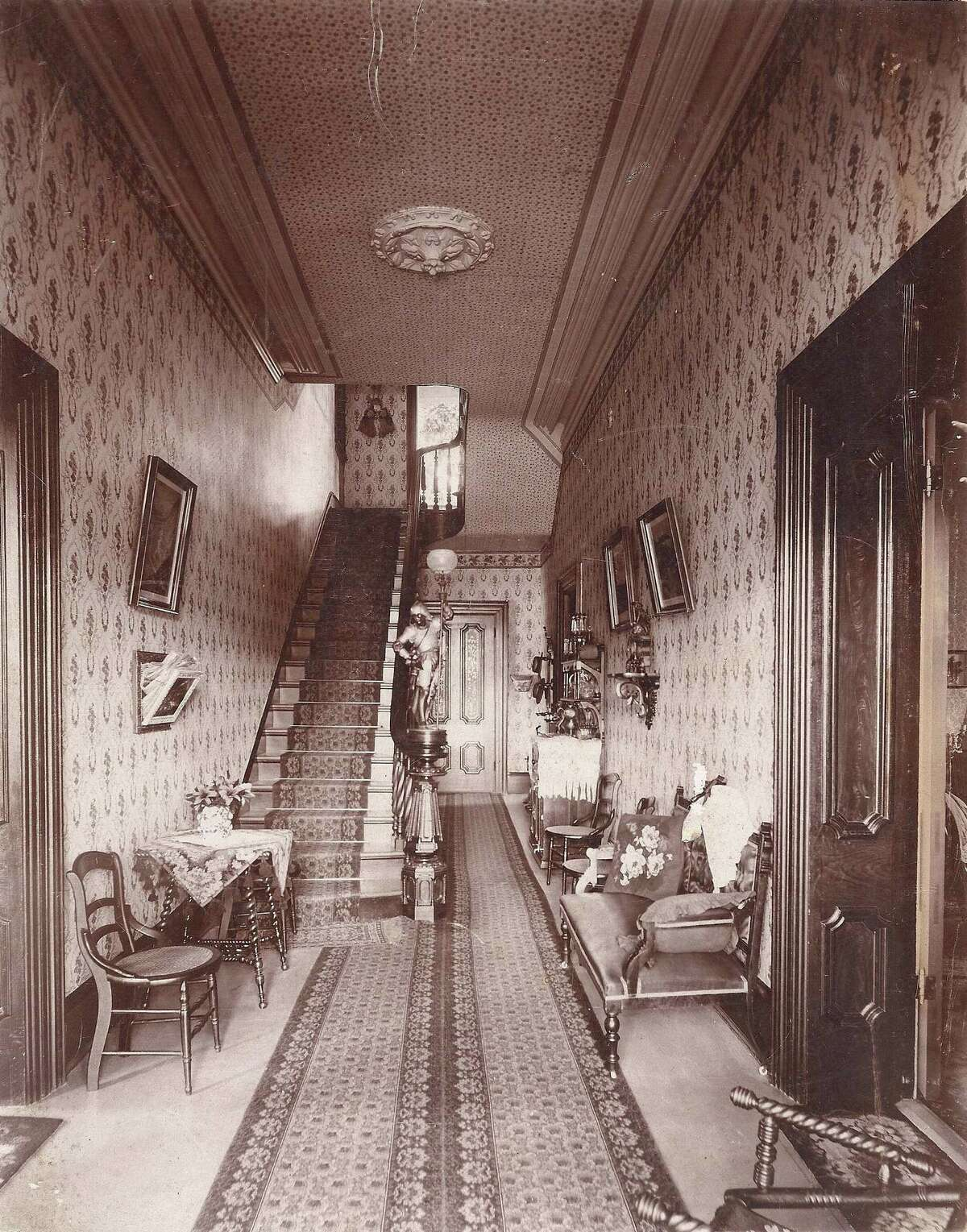 The entrance hall and stairway of the Steves Homestead in 1898. Visible is a carved stairway endpost, chairs, a settee and credenza and picture frames on the wall. Black and white. Please credit: Restricted Collection,