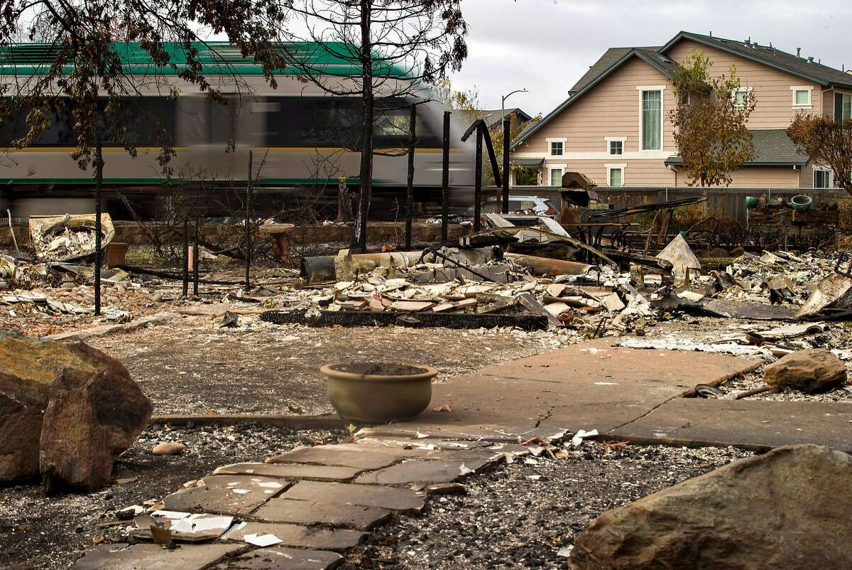 The Sonoma-Marin Area Rail Transit (SMART train) travels between a neighborhood that on one side is destroyed and the other intact on Thursday, Oct. 19, 2017, in Santa Rosa, Calif. The neighborhood was destroyed by the Sonoma County fires.