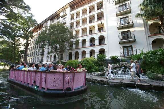 La Mansion del Rio is a popular tourist spot on the San Antonio River Walk. Here, one of the brand new barges with a new design passes by.
