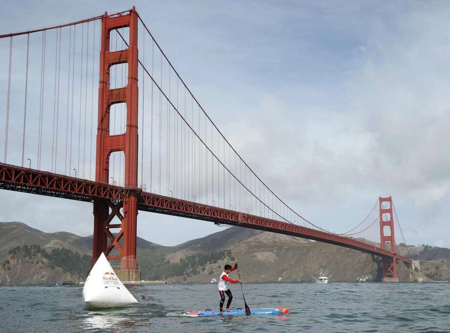 Second place winner Ryan Funk passes the final race buoy near the Golden Gate Bridge in the Red Bull Heavy Water stand-up paddleboard race in San Francisco, Calif. on Friday Oct. 20, 2017. Competitors began the course in the heavy surf off Ocean Beach and paddled through the Golden Gate to the finish line near the St. Francis Yacht Club. Photo: Paul Chinn / The Chronicle / ONLINE_YES