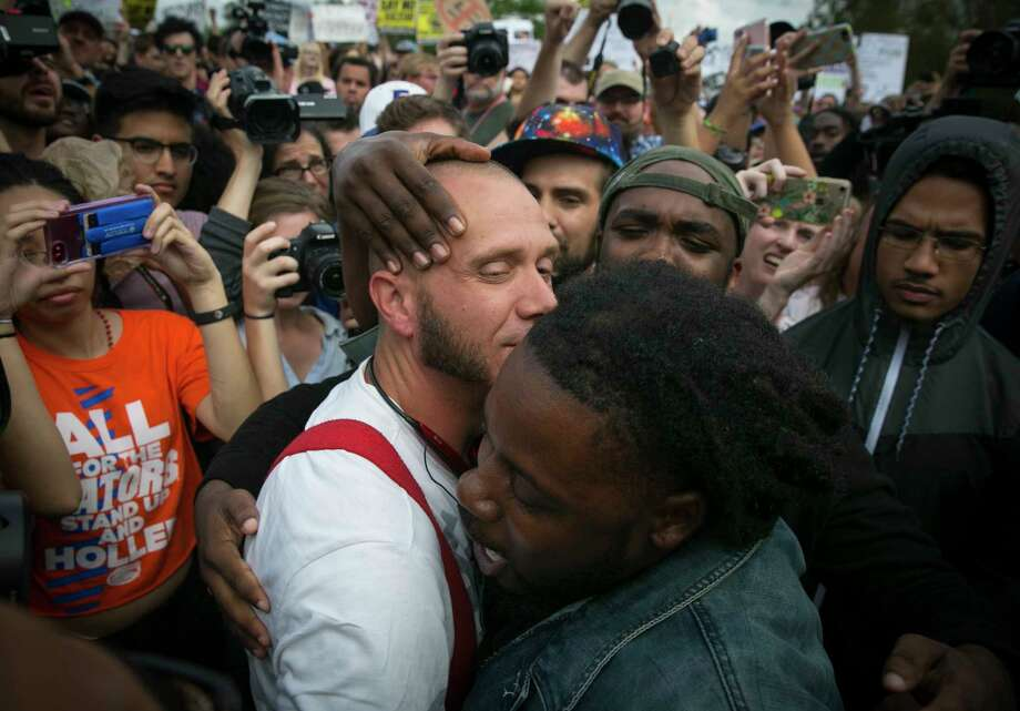 Aaron Courtney, right, a Gainesville, Fla., football coach, hugs Richard Spencer supporter Randy Furniss after asking Furniss why he hated him. Photo: NICOLE CRAINE, STR / NYTNS