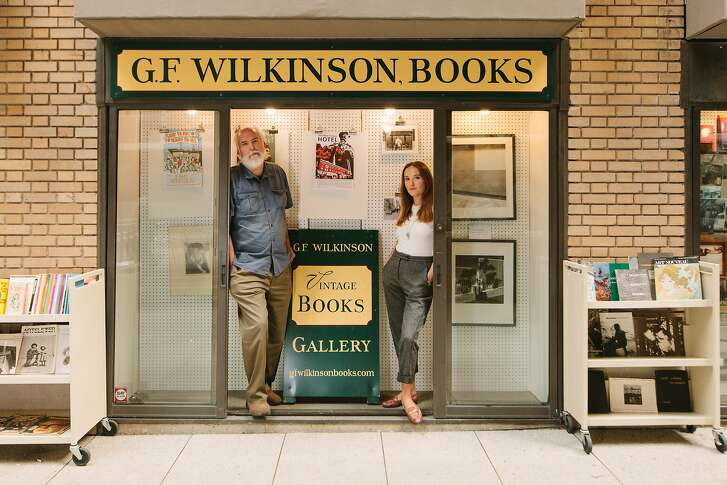 Rick Wilkinson and Natalia Kresich stand inside one of three window front panels that comprise G.F. Wilkinson Books at 34 Trinity Place in San Francisco, California, on October 11th, 2017. Wilkinson is transferring the lease on the bookstore to Kresich, originally a patron of the shop. He will continue to sell his stock out of one of the panels alongside Kresich, whose plans include hosting poetry readings by San Francisco based poets.