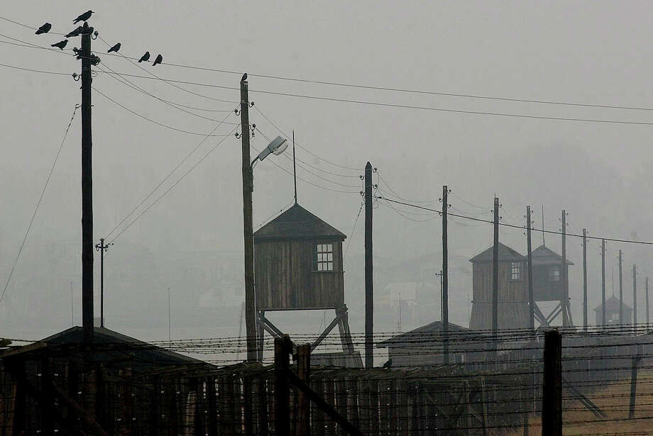 FILE - In this Nov. 9, 2005 file photo watch towers and the barbed wire fence of the former Nazi death camp Majdanek are photographed  outside the city of Lublin in eastern Poland. German prosecutors say friday, Oct. 20, 2017  they have charged a former guard at the Majdanek death camp with being an accessory to murder on allegations the 96-year-old served during a period when at least 17,000 Jews were killed.  (AP Photo/Czarek Sokolowski, file) Photo: Czarek Sokolowski, STF / AP2005