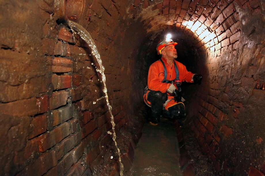 San Francisco Sewer serviceman Fred Gonzales works inside the sewer system under the 300 block of Ellis Street, which dates to 1866. Photo: Michael Macor, The Chronicle