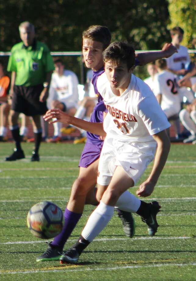 Ridgefield's Lucas Debarbieri, front, moves the ball upfield as Westhill's Chris Matrullo defends on Friday. Photo: Richard Gregory / Hearst Connecticut Media