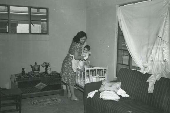 Edna Ramos puts her baby, Evangeline, to bed in the new apartment she and her husband, Roger, moved into in March 1941 at 1010 Collins St. in the Alazan Courts, San Antonio's first public housing project. They previously had shared cramped quarters with his family.