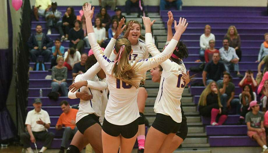 Members of the Westhill volleyball team celebrate after winning Game 1 against rival Stamford. Westhill went on to earn a thrilling 3-2 victory to claim the city championship Friday. Photo: Gregory Vasil / For Hearst Connecticut Media / Connecticut Post Freelance