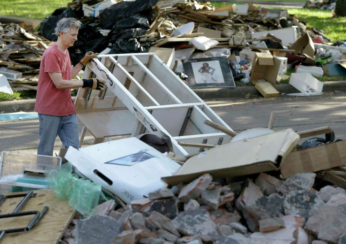 Jeff Lefkowitz piles debris in front of his flooded Meyerland home. The state wants to ensure haulers are working quickly to remove storm debris.
