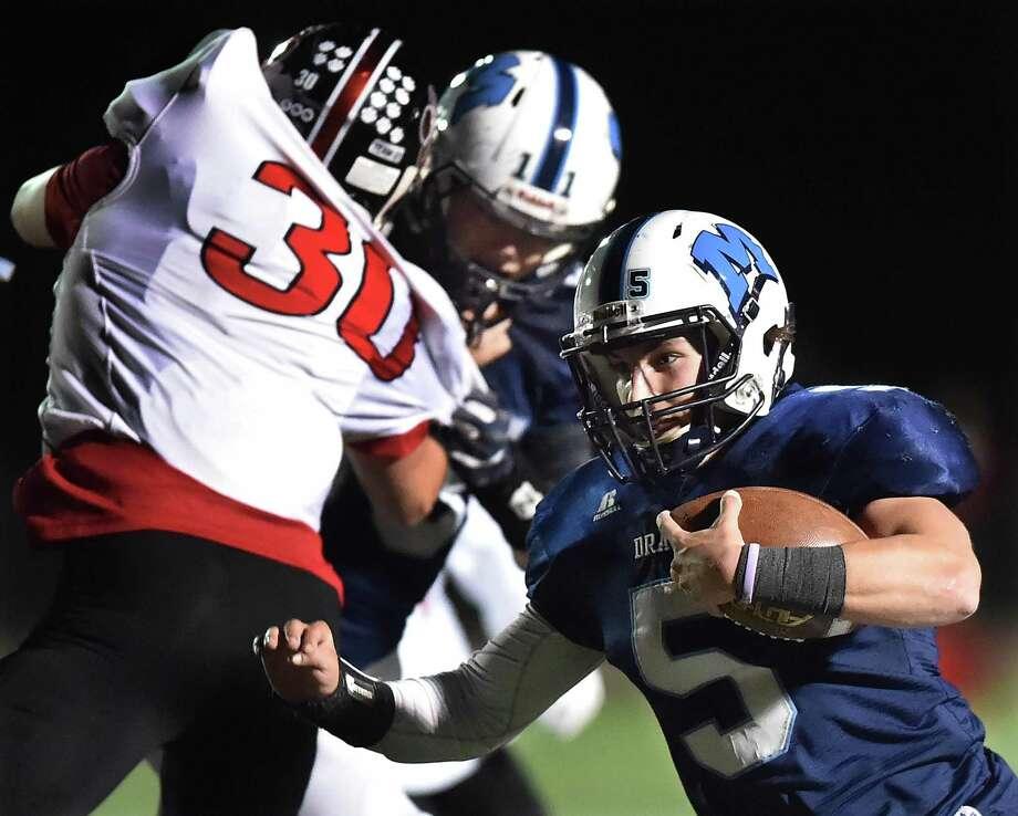 Middletown senior quarterback Stone Belzo gains yardage against E.O. Smith on Friday. Photo: Catherine Avalone / Hearst Connecticut Media / New Haven Register