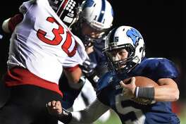 Middletown senior quarterback Stone Belzo gains yardage against E.O. Smith on Friday.