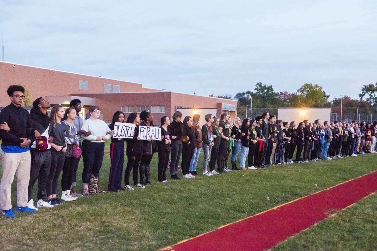 Students for Social Justice of Midland and members of WOMAN, the Women of Michigan Action Network, stood with their arms linked for a protest during the nation anthem on Friday at the Midland-Dow football game. (Danielle McGrew Tenbusch/for the Daily News)