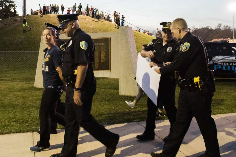 """A counterprotester is escorted from the stadium by police during a protest during the nation anthem on Friday at the Midland-Dow football game. Students for Social Justice of Midland representing both high schools stood with their arms linked to show """"opposition to racial oppression of people of color in the United States,"""" according to a statement on Facebook. (Danielle McGrew Tenbusch/for the Daily News) Photo: Danielle McGrew Tenbusch"""