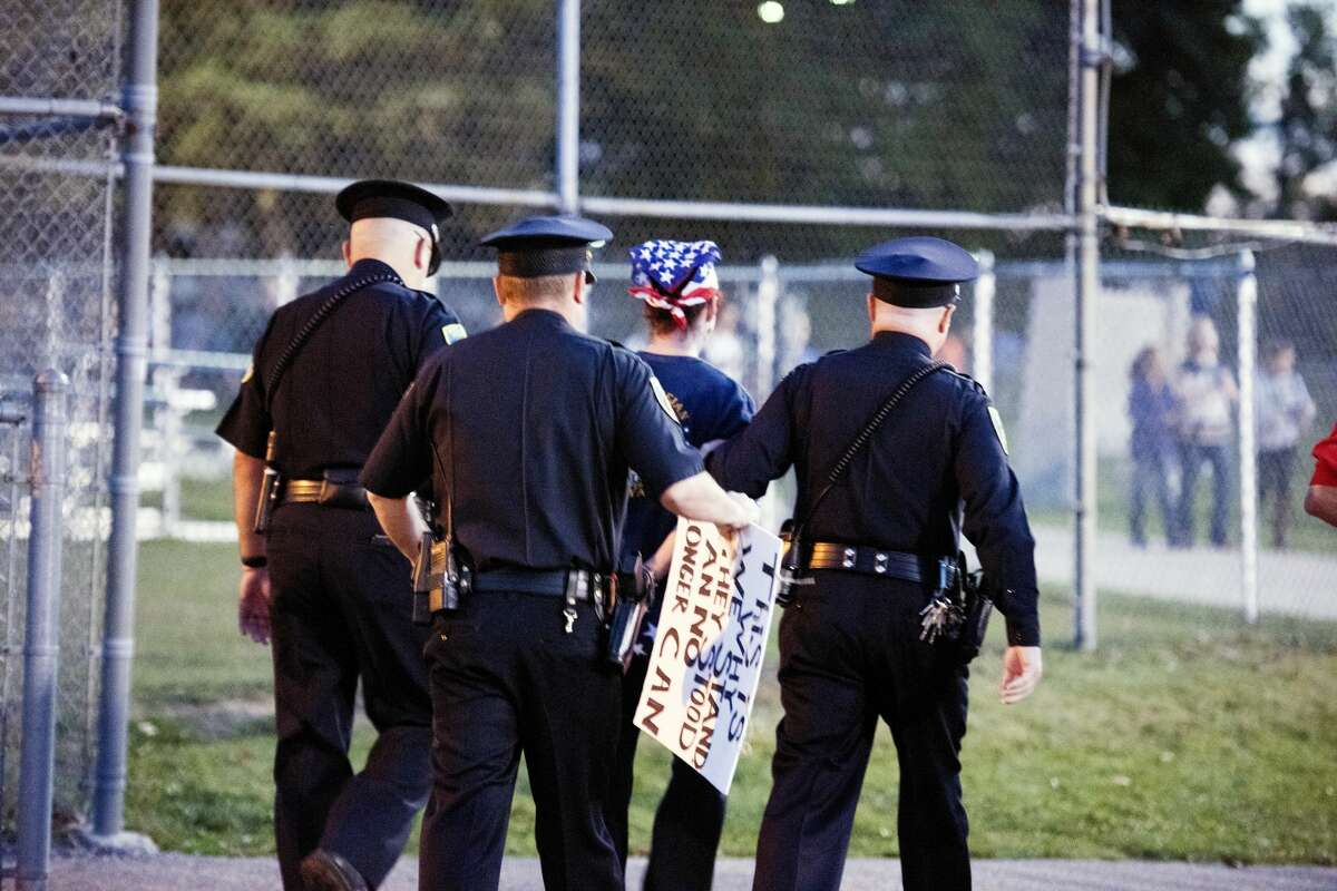 A counterprotester is escorted from the stadium by police during a protest during the nation anthem on Friday at the Midland-Dow football game. Students for Social Justice of Midland representing both high schools stood with their arms linked to show