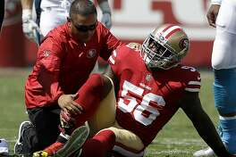 FILE - In this Sept. 10, 2017, file photo, San Francisco 49ers linebacker Reuben Foster (56) is tended to by a trainer after getting injured during the first half of an NFL football game against the Carolina Panthers in Santa Clara, Calif. The 49ers are hoping to get the talented rookie linebacker back this week after a sprained ankle sidelined him since the season opener. (AP Photo/Marcio Jose Sanchez, File)