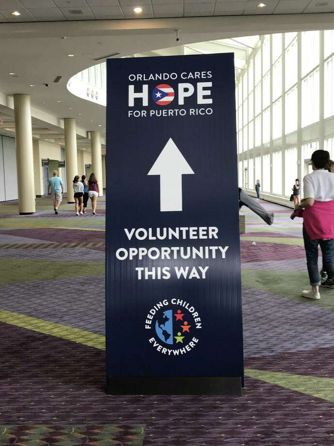 """Matt and Audrey Blondin participated in """"Orlando Cares - Helping Puerto Rico"""" with 30,000 other volunteers, packing boxes of supplies for residents of Puerto Rico, who are still dealing with the impact of Hurricane Maria. The Blondins, who have a vacation home in Orlando, were visiting the city the weekend of Oct. 7 to clean up the debris left by Hurricane Irma. Photo: Contributed Photo / Not For Resale"""