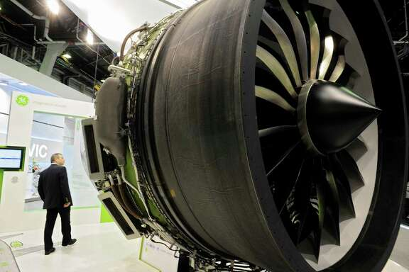 A visitor inspects a GE aircraft engine at the company's stand at the Paris Air Show in Paris. GE says it will sell off $20 billion worth of businesses in the next year or two.