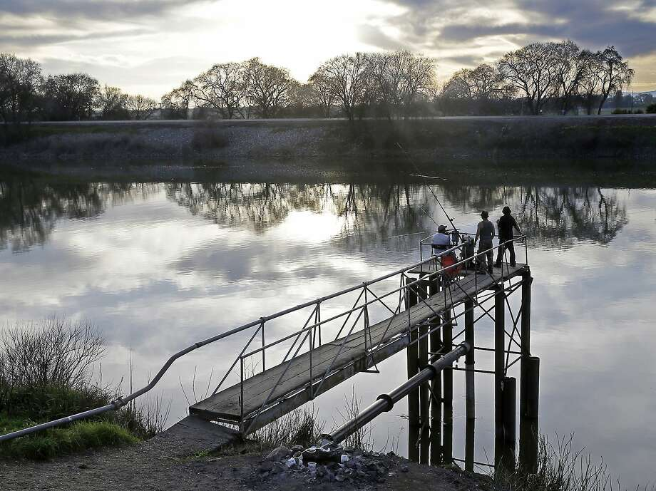 FILE - In this Feb. 23, 2016 file photo, people try to catch fish along the Sacramento River in the San Joaquin-Sacramento River Delta, near Courtland, Calif. The powerful Metropolitan Water District voted Tuesday, Oct. 10, 2017 to pay its share of the $16 billion project to build two massive tunnels to pipe water from Northern California to Southern California cities. The vote gives Gov. Jerry Brown's ambitious project an important boost of support after an influential agricultural group withdrew its support last month. The tunnels, which have been discussed in one form or another for generations, would pipe water around the Sacramento-San Joaquin Delta — where Sierra Nevada water flows toward the sea — to a system of canals that deliver water to farms and residents mostly in the southern half of the state. (AP Photo/Rich Pedroncelli, File Photo: Rich Pedroncelli, Associated Press