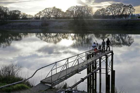 FILE - In this Feb. 23, 2016 file photo, people try to catch fish along the Sacramento River in the San Joaquin-Sacramento River Delta, near Courtland, Calif. The powerful Metropolitan Water District voted Tuesday, Oct. 10, 2017 to pay its share of the $16 billion project to build two massive tunnels to pipe water from Northern California to Southern California cities. The vote gives Gov. Jerry Brown's ambitious project an important boost of support after an influential agricultural group withdrew its support last month. The tunnels, which have been discussed in one form or another for generations, would pipe water around the Sacramento-San Joaquin Delta — where Sierra Nevada water flows toward the sea — to a system of canals that deliver water to farms and residents mostly in the southern half of the state. (AP Photo/Rich Pedroncelli, File