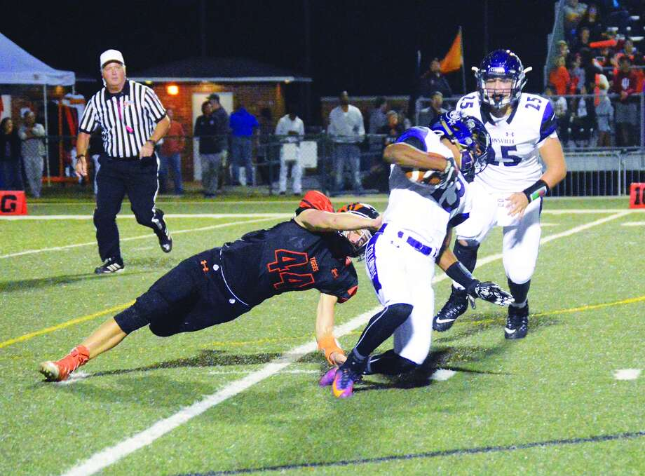 Edwardsville linebacker Ryan Strohmeier, left, brings down the Collinsville ball carrier late in the second quarter of Friday's Southwestern Conference game inside the District 7 Sports Complex.