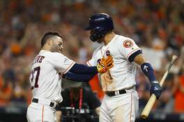 Houston Astros shortstop Carlos Correa (1) welcomes second baseman Jose Altuve (27) home after Altuve hit a home run in the eighth inning of Game 6 of the ALCS at Minute Maid Park on Friday, Oct. 20, 2017, in Houston. ( Brett Coomer / Houston Chronicle )