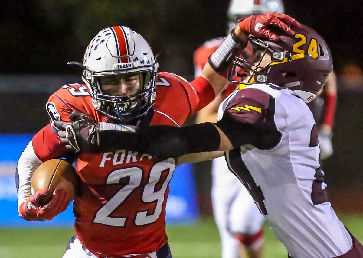 Foran's Mathew Cruz (29) tries to slip from the grip of Sheehan defender Evan Mansfield during Friday's game in Milford.