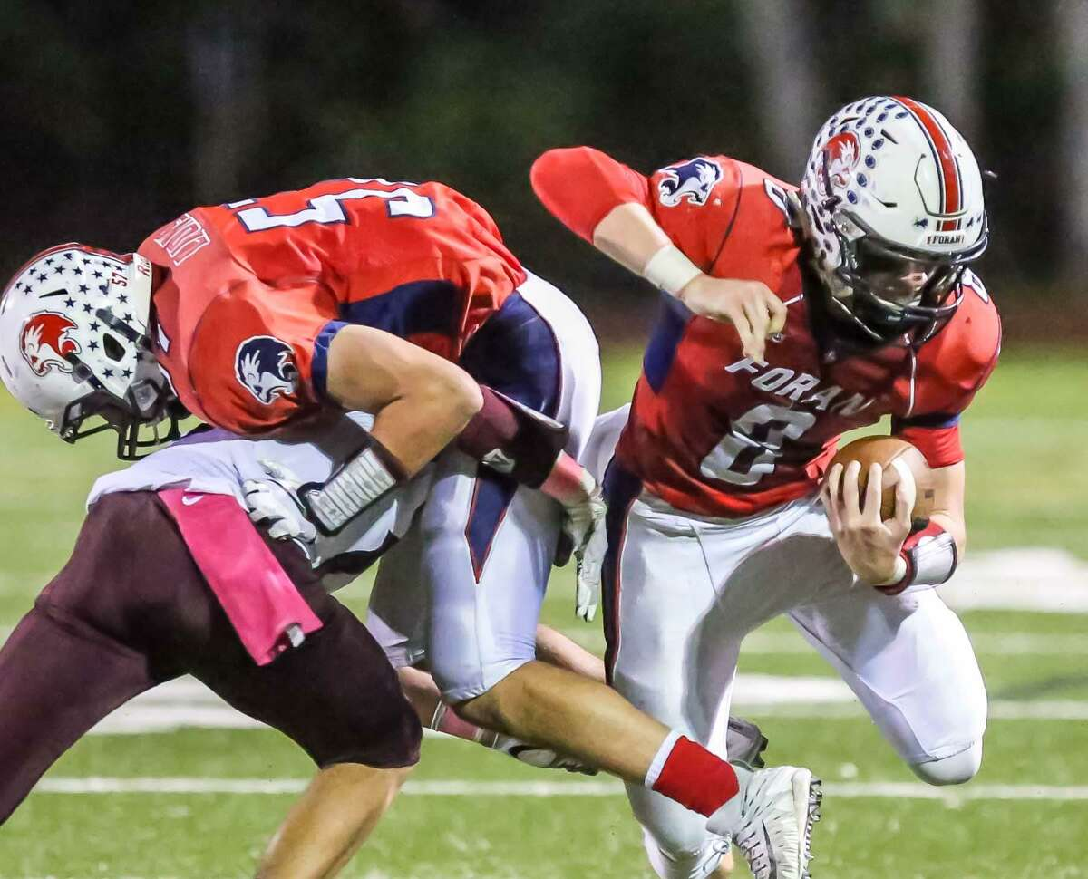 Foran's Jared Hubler (8) gets a key block by Justin DeEll on Sheehan's William Terzi during Friday's game in Milford.