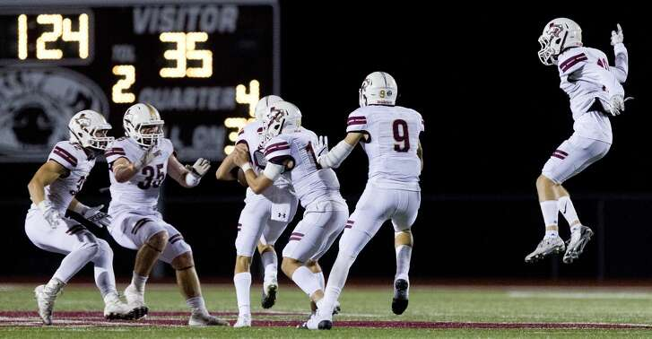 Magnolia West linebacker Peyton Martinez (22) is mobbed by teammates after intercepting a pass from Magnolia quarterback Reese Mason during the fourth quarter of a District 20-5A high school football game, Friday Oct. 20, 2017, in Magnolia.