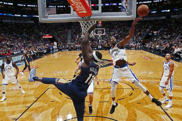Golden State Warriors forward Kevin Durant (35) blocks a shot by New Orleans Pelicans guard Jrue Holiday (11) in the first half of an NBA basketball game in New Orleans, Friday, Oct. 20, 2017. (AP Photo/Gerald Herbert)