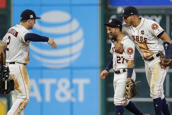 Houston Astros third baseman Alex Bregman (2), second baseman Jose Altuve (27) and shortstop Carlos Correa (1) celebrate the Astros win at the end of the ninth inning of Game 6 of the ALDS at Minute Maid Park, Friday, Oct. 20, 2017, in Houston. ( Karen Warren / Houston Chronicle )