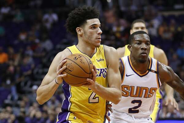 Los Angeles Lakers guard Lonzo Ball, left, drives past Phoenix Suns guard Eric Bledsoe during the first half of an NBA basketball game, Friday, Oct. 20, 2017, in Phoenix. (AP Photo/Matt York)