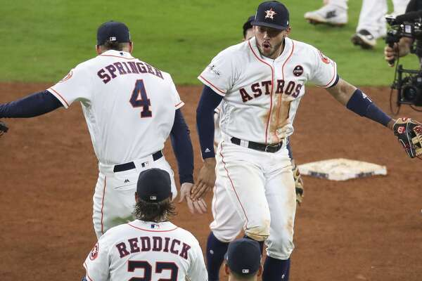Houston Astros center fielder George Springer (4) and shortstop Carlos Correa (1) celebrate as they beat the New York Yankees 7-1 in Game 6 of the ALCS at Minute Maid Park Friday, Oct. 20, 2017 in Houston. ( Michael Ciaglo / Houston Chronicle)