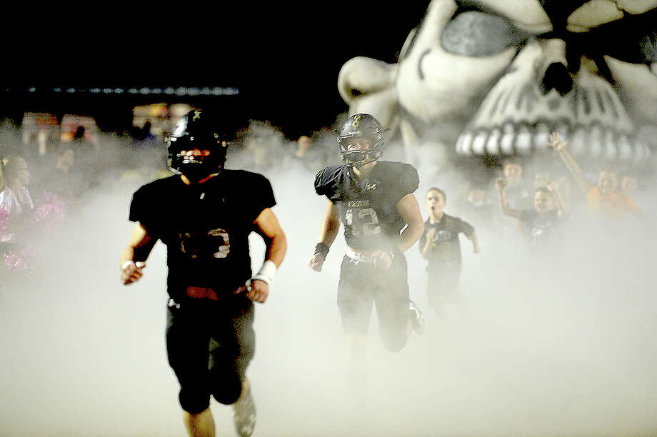 Vidor's Pirates burst onto the field from their fog-shrouded inflatable to face Port Neches - Groves' during their District 22 - 5A match-up Friday night in Vidor. Photo taken Friday, October 20, 2017 Kim Brent/The Enterprise Photo: Kim Brent / BEN