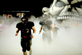 Vidor's Pirates burst onto the field from their fog-shrouded inflatable to face Port Neches - Groves' during their District 22 - 5A match-up Friday night in Vidor. Photo taken Friday, October 20, 2017 Kim Brent/The Enterprise