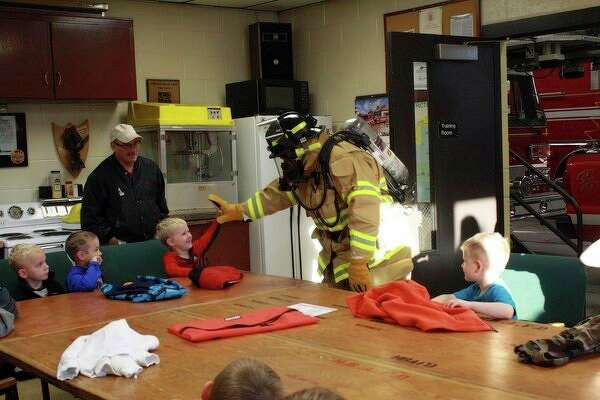 Several groups of preschoolers from Our Lady of Lake Huron stopped by the Harbor Beach Department this week to learn about fire equipment and fire safety. Each child received a replica fire helmet for their own personal use. (Rich Harp/For the Tribune)