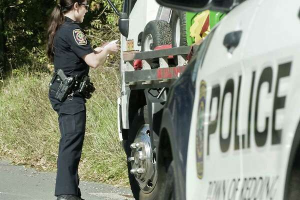 Redding police officer Jenna Matthews checks the information of this vehicle on Lonetown Road. Redding, Watertown and Waterbury Police chiefs have been developing a program, called Breaking Barriers, that would improve relations between the community and police officers at traffic stops. Wednesday, Oct. 18, 2017