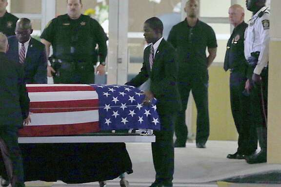 The casket of Sgt. La David T. Johnson of Miami Gardens, who was killed in an ambush in Niger. is wheeled out after a viewing at the Christ The Rock Church, Friday, Oct. 20, 2017  in Cooper City, Fla. (Pedro Portal/Miami Herald via AP)