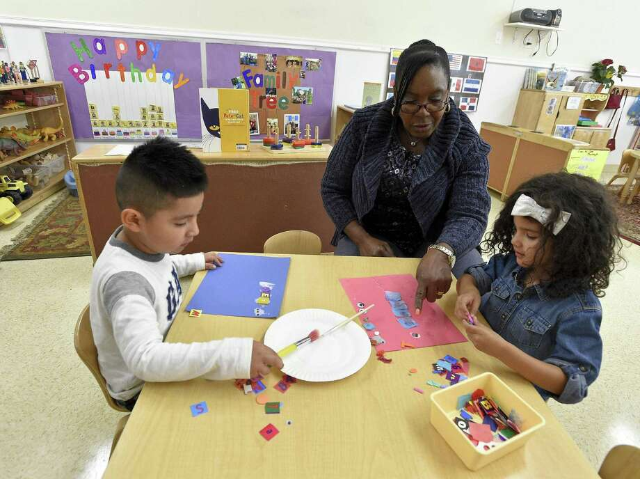 Dawn Medley, a teacher at the Children's Learning Center, works with pre-K students Johncarlos and Aliyah as they work on an art project in class at the early childhood education center in Stamford, Connecticut on Thursday, Oct.19, 2017. Photo: Matthew Brown / Hearst Connecticut Media / Stamford Advocate