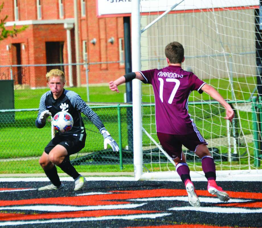 Edwardsville keeper Michael Hoelting, left, chases down a loose ball before Belleville West's Brayden Easton can get to it in the second half.