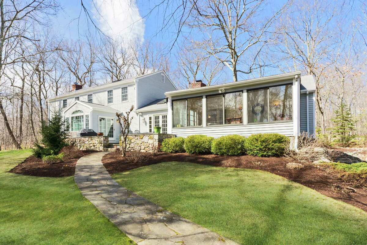 The Georgian Revival colonial at 374 Thayer Pond Road in the Lake Club neighborhood of Wilton is on more than 2 acres with professional landscaping. The home's sunroom has French doors that open to a fieldstone terrace.