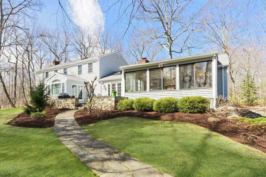 The Georgian Revival colonial at 374 Thayer Pond Road in the Lake Club neighborhood of Wilton is on more than 2 acres with professional landscaping. The home's sunroom has French doors that open to a fieldstone terrace. Photo: Coldwell Banker Residential Brokerage / ONLINE_CHECK