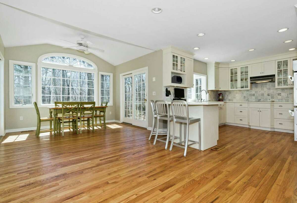 Above: The all-white gourmet chef's kitchen has stainless steel appliances and seating at both the island and an adjacent breakfast room. Below: Located in the Lake Club section of Wilton, 374 Thayer Pond Road is conveniently located minutes from the centers of Wilton and New Canaan.