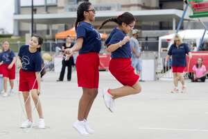 New Caney Elementary jump rope team member Giselle Zavala, right, jumps rope with Abigail Guzman during the annual Fire and Ice Festival at Texan Drive Stadium, Saturday, Oct. 21, 2017, in New Caney.