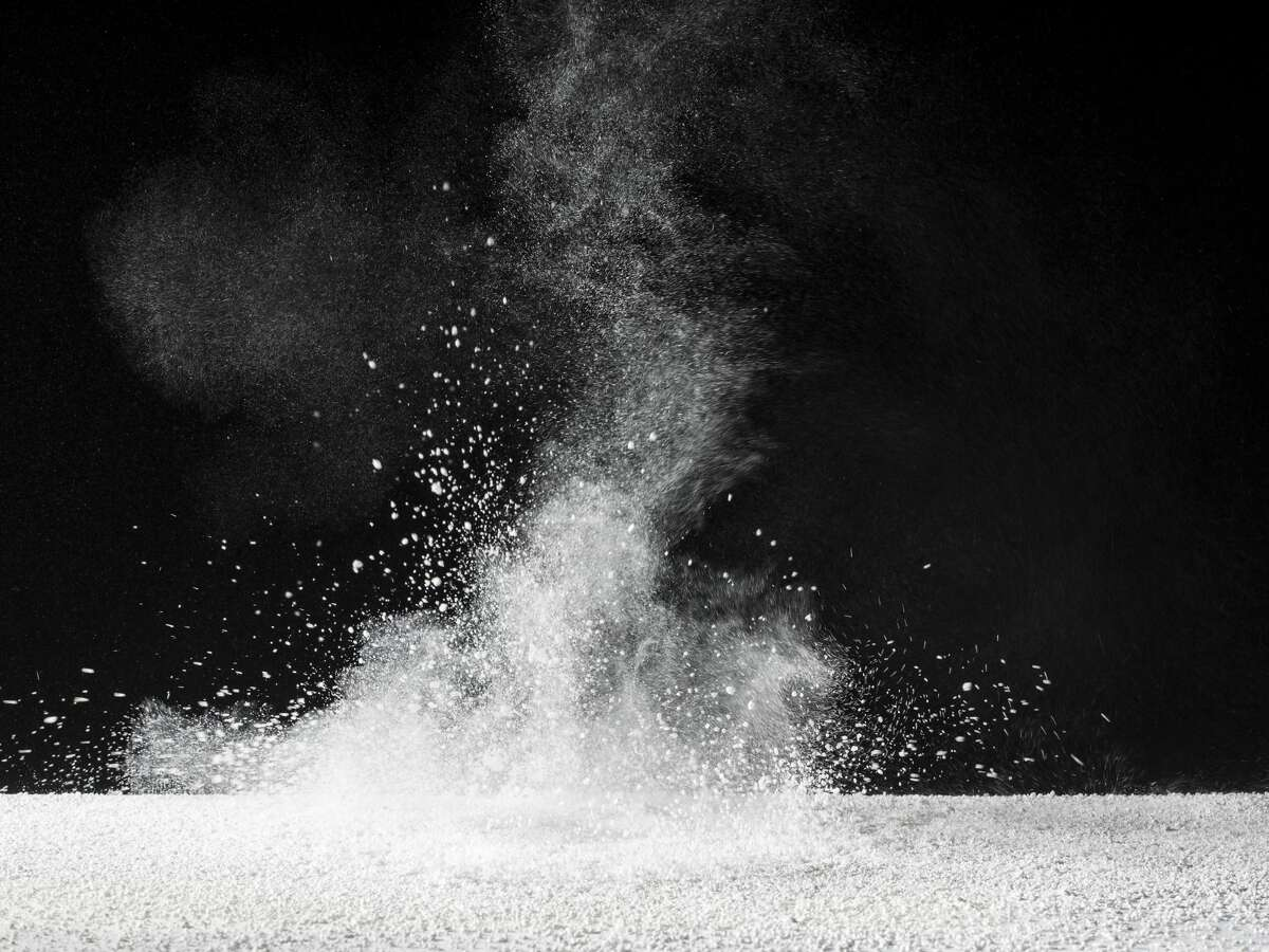 Particles of powder of talc on a black bottom. Photo of study