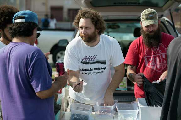 Chad Cain, center, and Jed Gettman, right, hand out supplies and clothing donated to homeless citizens by South Texas Atheists for Reason, Sunday, Sept. 24, 2017, in Downtown San Antonio. (Darren Abate/For the San Antonio Express-News)