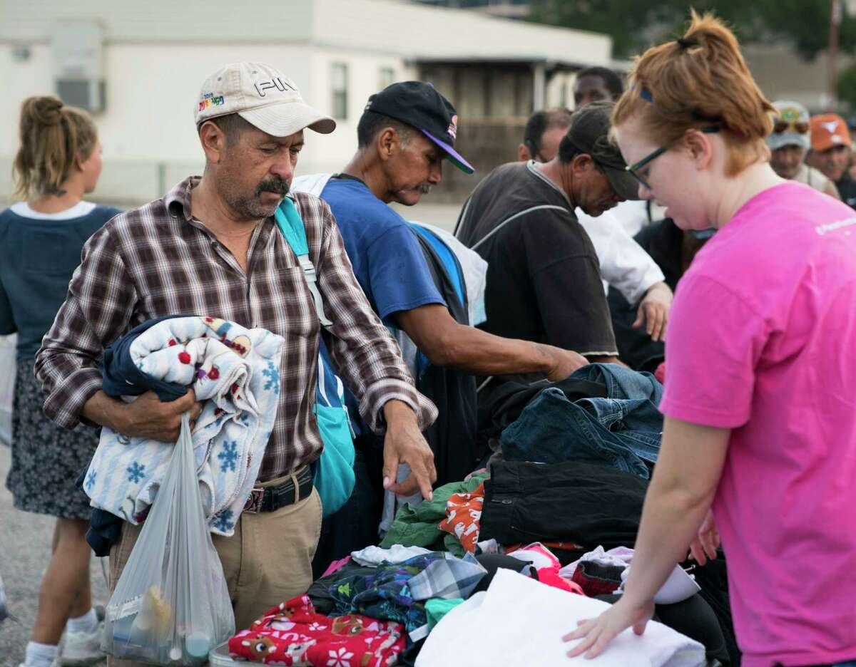 Cole Harvey, right, helps Miguel Rodriguez select clothing donated to homeless and other citizens in need by South Texas Atheists for Reason, Sunday, Sept. 24, 2017, in Downtown San Antonio. (Darren Abate/For the San Antonio Express-News)